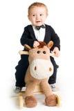 Baby in rok op hobbelpaard Stock Fotografie
