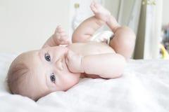 Baby-Rollen auf dem Bett, spielend Lizenzfreies Stockbild