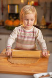 Baby rolling dough in christmas decorated kitchen Royalty Free Stock Image