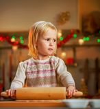 Baby rolling pin dough in christmas decorated kitche Royalty Free Stock Photo