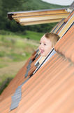 Baby in the roof window Stock Photography