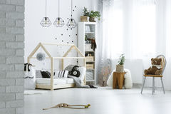 Baby room with brick wall. Bed, lamps, bookcase and chair Royalty Free Stock Images
