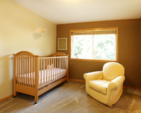 Baby room with crib and yellow chair. Baby room with crib and yellow chair and brown walls Royalty Free Stock Photo