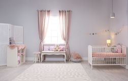 Baby room interior with comfortable crib. And indoor bench Royalty Free Stock Photography