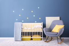 Baby room interior with crib and rocking chair. Near wall Stock Image