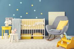Baby room interior with crib and rocking chair. Near wall Stock Photo