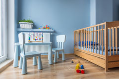 Baby room in light blue color. Spacious baby room with wooden furniture, cot, blue walls and wooden floor panels Stock Image