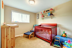 Baby room with red stained wood crib and bright interior. stock images