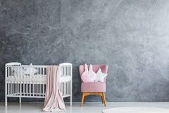 Baby room with white crib. Modern baby room interior with white crib and pink armchair against grey, empty wall Royalty Free Stock Photos