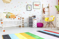 Baby room with yellow chair. And white cot Stock Photos
