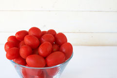 Baby rosa tomatoes on white. Bunch of baby rosa tomatoes in glass bowl on white background Stock Images