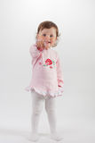 Baby  in rose dress pointing at camera smiling Royalty Free Stock Photo