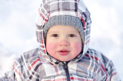 Baby with rosy cheeks in winter outdoors Stock Image