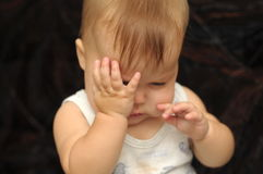 Baby rubbing his eyes Stock Photo