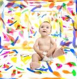 Baby in ruimte met kleuren op muren Stock Foto's