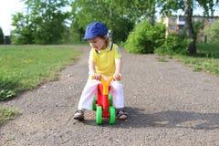 Baby on run bike in summer. Baby on plastic run bike outdoors in summer Royalty Free Stock Image
