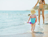 Baby running to mother along seashore Royalty Free Stock Image