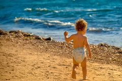 Baby running towards the waves Stock Image