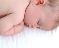 Baby's Asleep. Closeup of sleeping baby lying on white blanket in a comfortable position Stock Images