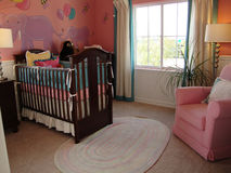 Baby's Bedroom. Beautiful baby's bedroom in pink and purple colors, pink rocking chair Stock Photography