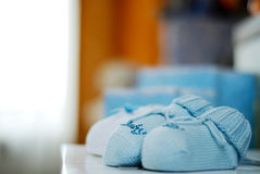 Baby's bootee. Dark blue baby's bootee on a shelf in a nursery, brightly lighted up light from a window Stock Photos