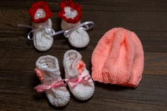 Baby's bootee and cap on wooden. Background Royalty Free Stock Photos