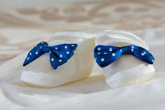 Baby`s bootees on a bed. White baby`s bootees with blue bow on a white sheet stock images