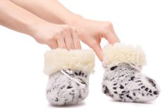 Baby`s bootees fur warming in female hands. On a white background isolation Royalty Free Stock Images