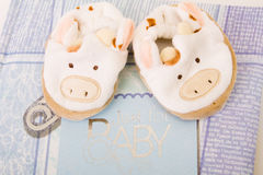 Baby's booties against blue photoalbum Royalty Free Stock Image