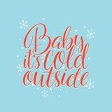 Baby, it`s cold outside. Hand drawn holiday lettering with snowflakes on a blue background Stock Photos