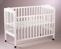 Baby's cot. Wooden baby's cot on th plain background Royalty Free Stock Image