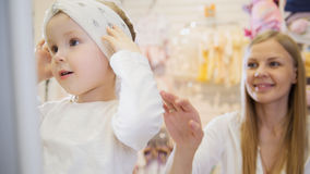 Baby`s dress store - little blonde baby girl with mother doing shopping and buying pretty hat Stock Photos