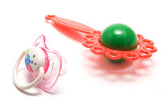 Baby's dummy and rattle. Isolated baby's dummy and rattle Royalty Free Stock Image