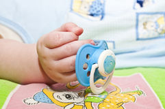 Baby's dummy, soother. Soother in the  sleeping baby hand Royalty Free Stock Images