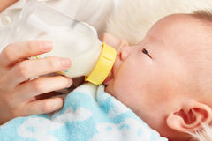 Baby's feeding. Baby is feeding milk from baby's bottle Royalty Free Stock Image