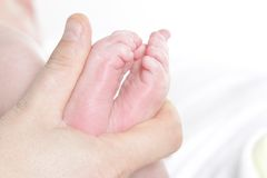 Baby's feet in father's hand Stock Photos
