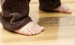 Baby's feet on the floor. (first steps Royalty Free Stock Photography