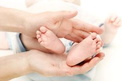 Baby's feet in parent's hands Stock Photo