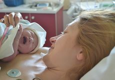 Baby`s first cry. Mother and newborn after childbirth. Baby`s first cry. The first moments of mother and newborn after childbirth Royalty Free Stock Photo