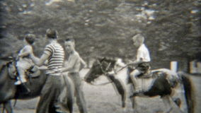1949: Baby's first horse ride with dad holding for safety. NEWARK, NEW JERSEY. Vintage 8mm film home movie professionally cleaned and captured in 4k (3840x2160 stock video