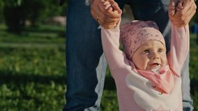Baby`s first steps. Dad helps to take the first steps his daughter stock footage