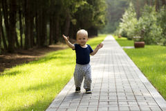 Baby`s first steps.The first independent steps. Cute boy on the walk Stock Image
