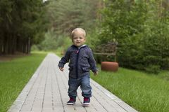 Baby`s first steps.The first independent steps. Running toddler in the park stock photo