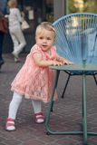 Baby`s first steps.The first independent steps. Baby girl walking in the park with chair support Stock Photos