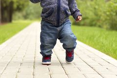Baby`s first steps.The first independent steps. Running toddler in the park royalty free stock photo
