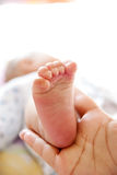Baby's foot in a hand Stock Image