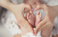 Baby's foot in mother hands. Newborn baby feet in mother hands.Masseur massaging little baby's foot, shallow focus. Newborn baby feet in mother's hands.Mother stock image