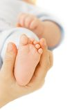 Baby's foot in parent's hand Stock Images