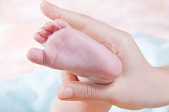 Baby's foot in woman hands Stock Photography