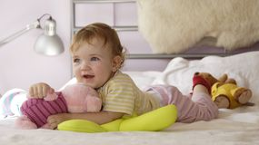 Baby's game. A baby is playing on a bed royalty free stock photos